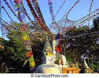 Small stupa with colorful buddhist flags of Swayambhunath temple complex. Kathmandu, Nepal.