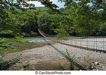 Small suspension bridge through river Belaya in Republic of Adygea, Russia