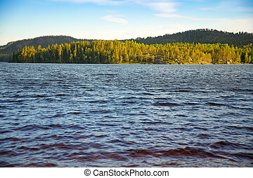 Small swedish lake and forest at sunset lights in Sweden