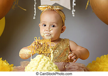 small sweet baby girl in a golden dress with a bow on her head trying a jazzy jelly cake from a cream. studio shot of a birthday on a gray background surrounded by balls