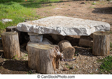 Small table made of tree trunks and a stone plate