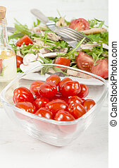 Small tomatoes in a glass jar with seasonal salad