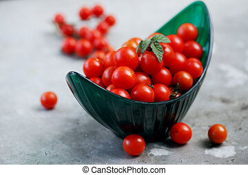 small tomatoes in a green bowl