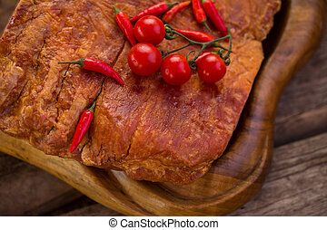 Small tomatoes on meat piece.