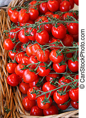Small and juicy tomatoes in a basket at the market.