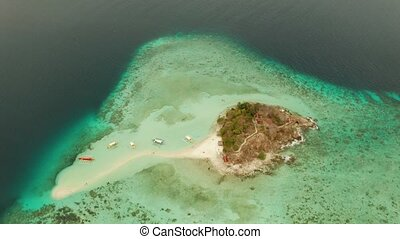 Small torpic island with a white sandy beach, top view.