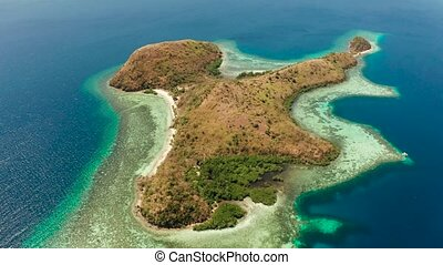 Small torpical island with white sandy beach, top view.