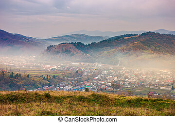 small town in hazy valley on gloomy afternoon - autumn...