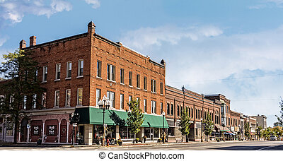 A photo of a typical small town main streetin the United States of America. Features old brick buildings with specialty shops and restaurants. Decorated with autumn decor.