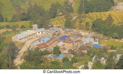 Small town on foothill from above . View from air of small and poor town placed on green land of Himalayan valley, Nepal. Local houses in Nagarkot