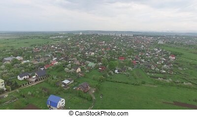 Small town with low houses in spring nature. Aerial view