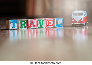 Small toy car and wooden blocks spelling travel