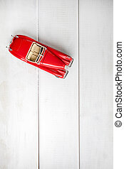 Small toy car on a white wooden background.