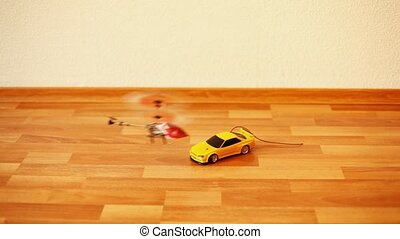 toy helicopter flies over toy machine going on floor - small...