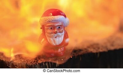 small toy plastic Santa Claus melts under the powerful hot flame of fire. Slow motion