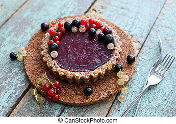 Small vegan tarts made of nuts and berry jam decorated with black, red and white currants on cork board