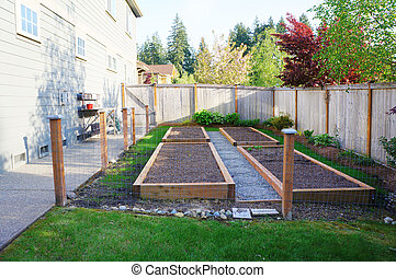 Small vegetable garden in the fenced backyard near house. -...