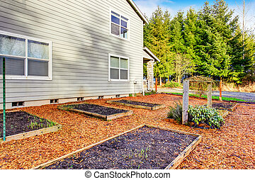 Small vegetable garden with risen beds in the fenced backyard near house. Northwest, USA