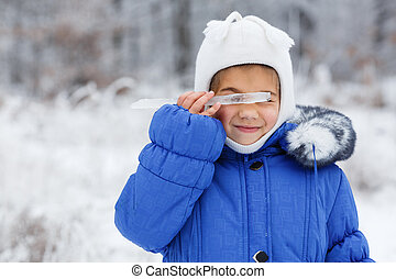 Small very cute girl in winter on the background of snowy sunset forest, close up