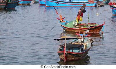small vietnamese fishing boats roll in sea bay at dawn
