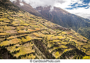 Small village in the mountains, surrounded by farm fields