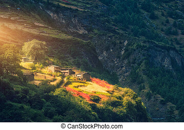 Small village on the hill lighted by a sunbeam at sunset