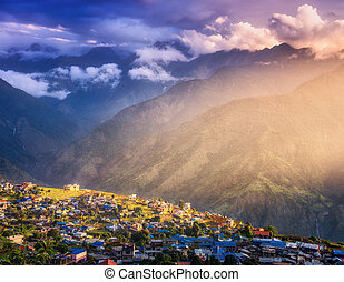 Small village on the hill lighted by a sunbeam at sunset in Nepal