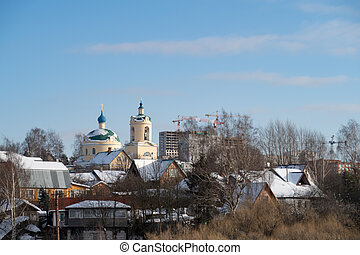 Small village with a church, new buildings in the background, winter, background