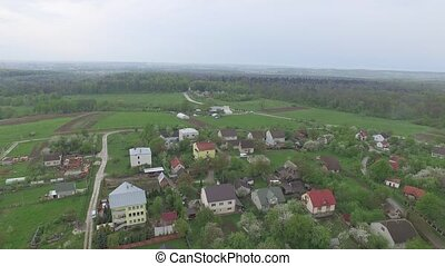 Small village with low houses near the forest. Aerial view