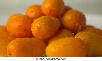 Small water drops hit heap of orange kumquat. Super slow motion video