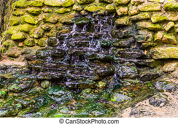small water fall in a garden, water streaming over a wall of rocks, backyard architecture