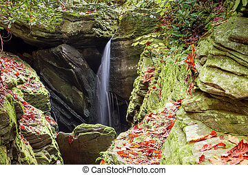 small waterfall in a narrow rocky gorge in the North Carolina mountains in autumn
