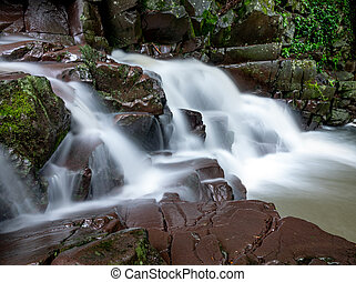 Small waterfall in the forest at autumn