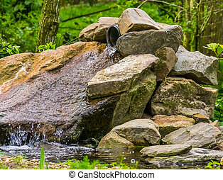 small waterfall made out of boulders in a garden, simple and beautiful garden architecture, pond decorations, nature background