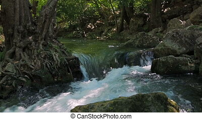 small waterfall near the collapse of stones - a small...
