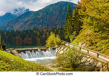 Lago de Fusine in the mountain valley - Small waterfall on...