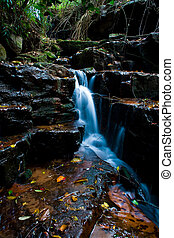 small waterfall - a small waterfall flowing between the...