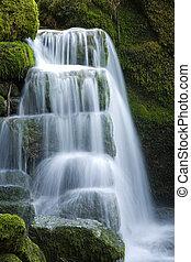 small waterfall - A small waterfall over moss rocks.