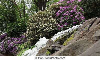 waterfall with blossom flowers in botanic garden - Small...