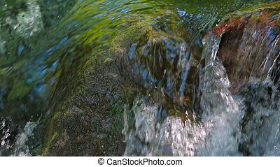 small waterfall with rocks in the water - a small waterfall...