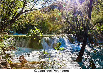 small waterfall with sunlight rays in Plitvice Lakes...