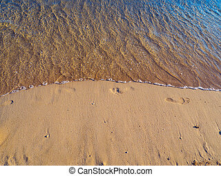 Small wave washing away footprints in the sand - on the beach
