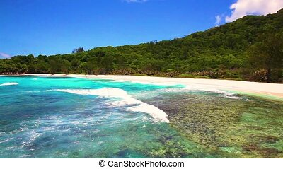 small waves and white beach at Seychelles islands. La Digue,...