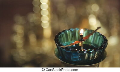 Small wax candle burns on candlestick in temple indoors....