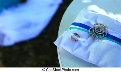 Small wedding table with decor and rings on wedding ceremony