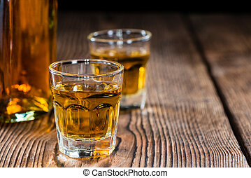 Small Whiskey shot on an old wooden table