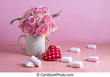 Small white and pink marshmallows are scattered on a pale pink background next to a vase of roses. Place for text.
