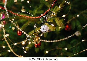 Small white ball-bell on the branches of a Christmas tree in garland lights.