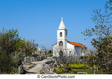 Small white church on a sunny day with blue sky