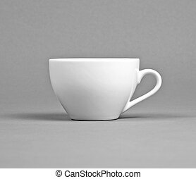 Small white coffee cup on a gray background.